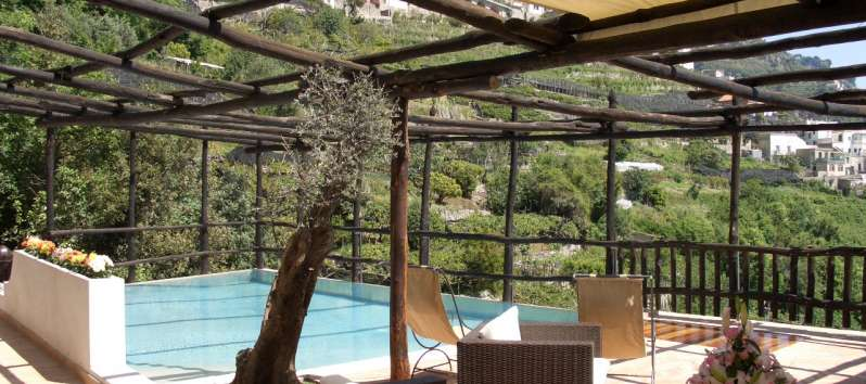 Villa Anouk terrace equipped with deck chairs and garden furniture, shaded by a pergola