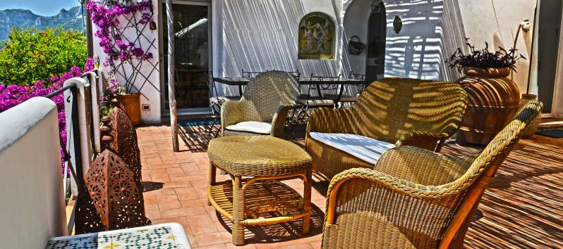 Villa Apollo terrace is decorated with large terracotta vases and a set of wicker furniture