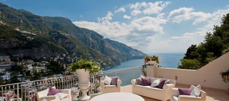 terrace with sofas and table with sea view in the villa in Positano