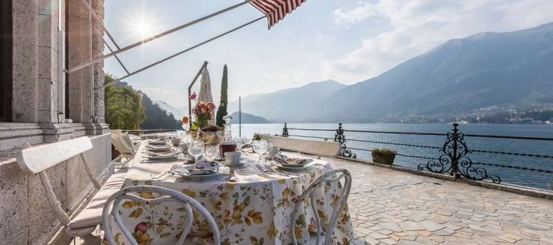terrace with dining table and lake view in the villa in Bellagio