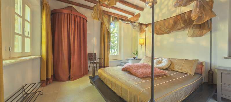 double bedroom with exposed beams in the villa on Lake Como