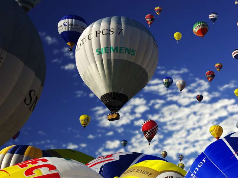 Hot air balloons float over the beautiful Italian countryside