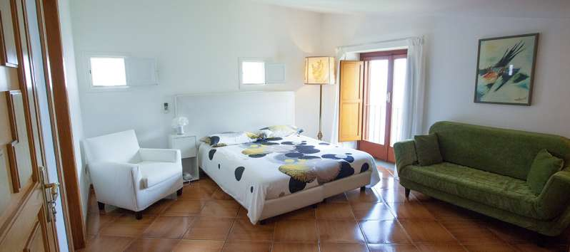 double bedroom with sofa and armchair in the villa with swimming pool on the Amalfi Coast