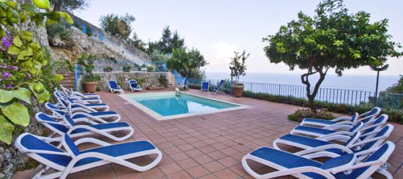 swimming pool with deckchairs and sea view in the villa in Amalfi