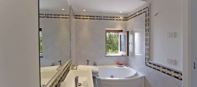 bathroom with tub and mirror in the villa in Amalfi
