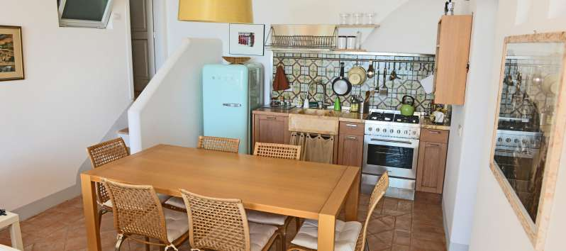 kitchen with wooden table in the villa with pool in Praiano