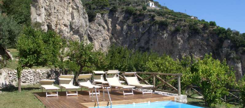 swimming pool with deck chairs and panoramic view in the villa in Amalfi