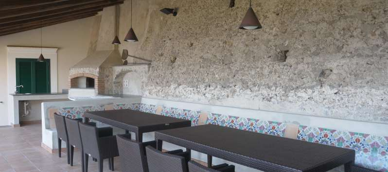outdoor tables with fireplace in the villa with pool in Amalfi