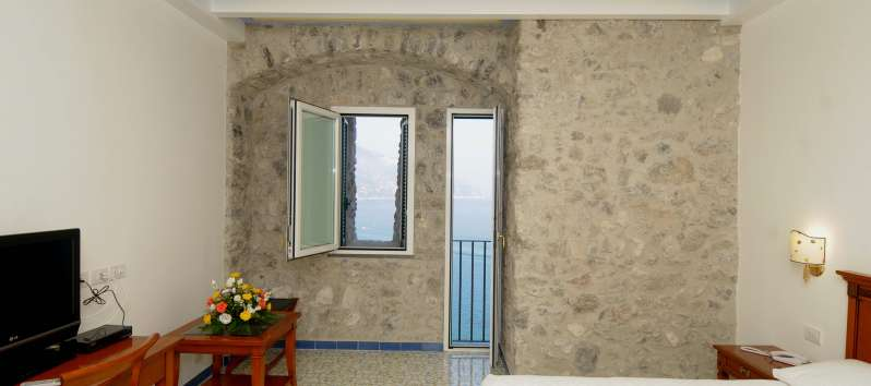 bedroom with balcony and sea view in the villa with pool in Amalfi