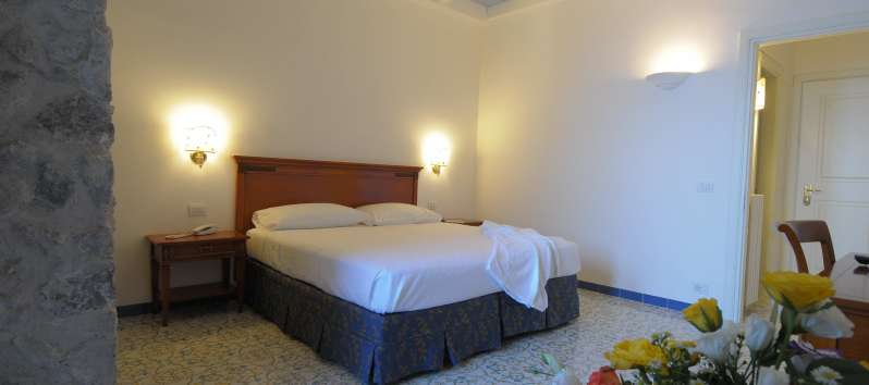 double bedroom with exposed beams in the villa with pool in Amalfi