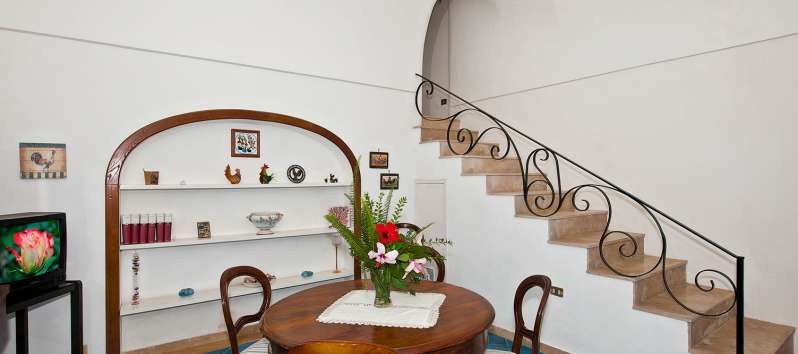 dining room with wooden staircase in the villa in Positano