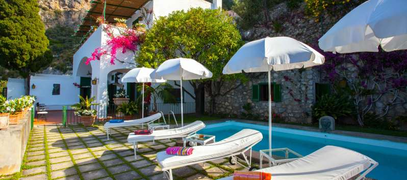 swimming pool with umbrellas and deckchairs in the villa on the Amalfi Coast