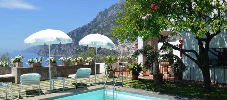 swimming pool with umbrellas and sea view in the villa on the Amalfi Coast