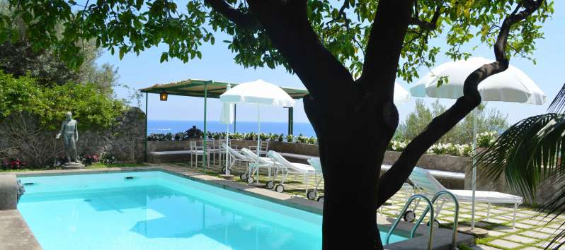 swimming pool with deckchairs and umbrellas in the villa on the Amalfi Coast