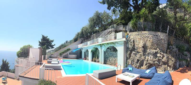 swimming pool with deckchairs and sea view in the villa on the Amalfi Coast