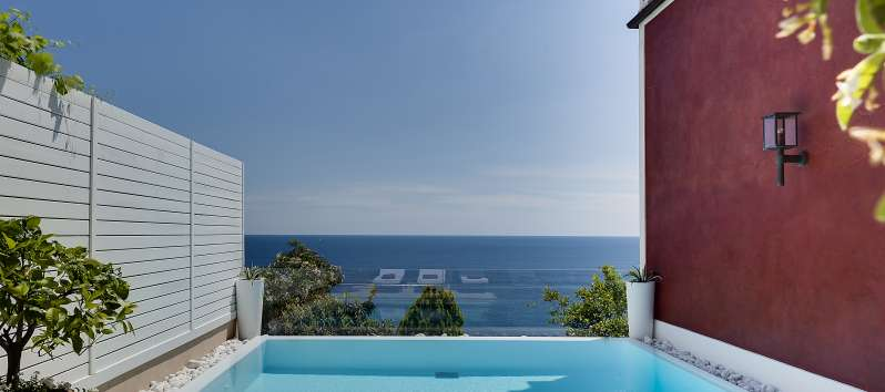 swimming pool with deckchairs and sea view in the villa in Praiano