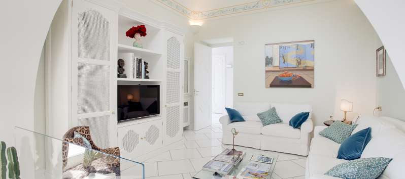 living room with sofa and TV in the villa with swimming pool in Praiano