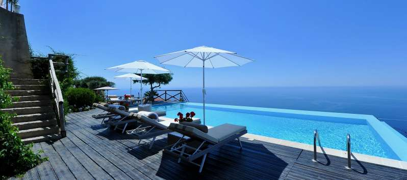 swimming pool on the sea with deckchairs and umbrellas in the villa on the Amalfi Coast