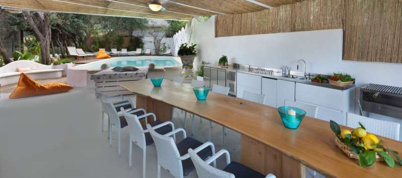 outdoor kitchen with table and pool in the villa with sea view in Sorrento