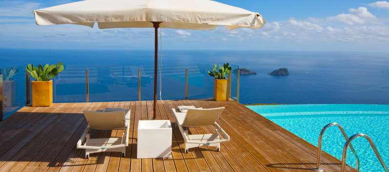 swimming pool with umbrella and deck chairs and sea view in the villa in Sorrento