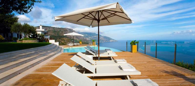 deck chairs and umbrella in the villa with pool in Sorrento