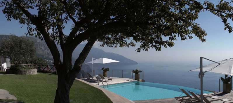 swimming pool with umbrella and sea view in the villa in Sorrento