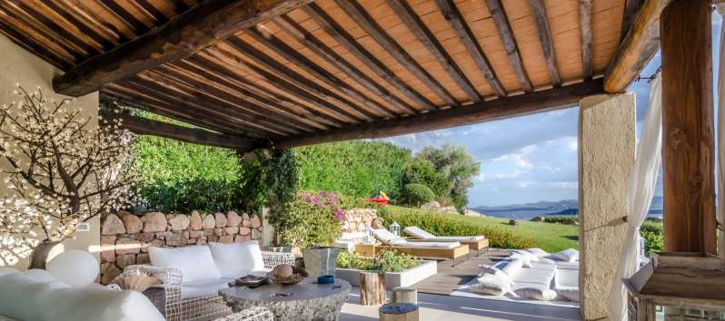 covered terrace with sofas in the villa with pool in Costa Smeralda