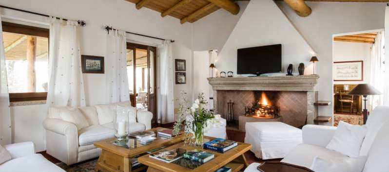 living room with fireplace in the villa with swimming pool in Sardinia