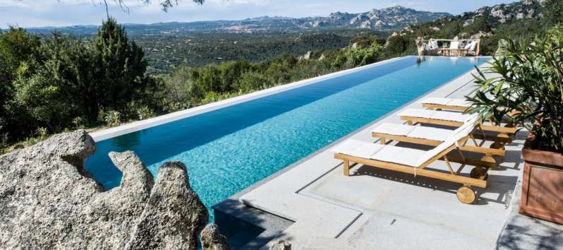 swimming pool with panoramic view and deckchairs in the villa in Sardinia