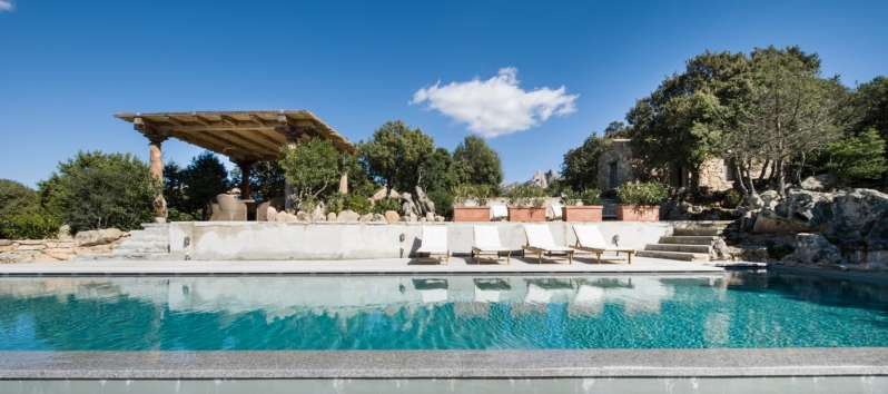 swimming pool with deckchairs in the villa in Sardinia