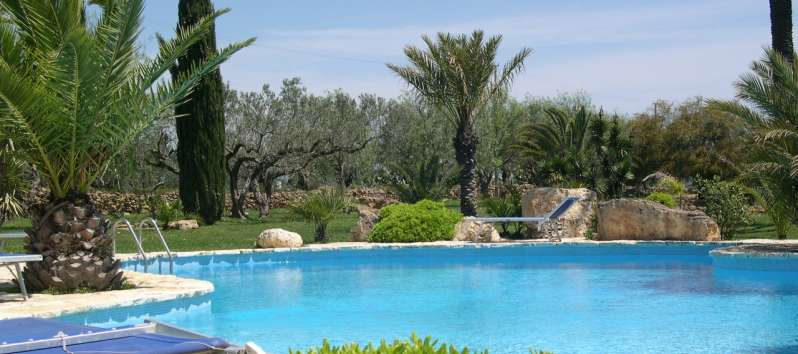 Villa Bahira surrounded by a garden with cypresses, palms and olive trees