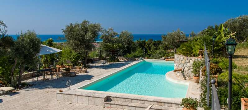 swimming pool with deckchairs and sea view in the villa in Sicily