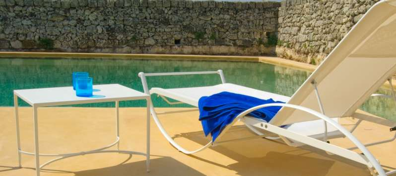 deckchairs with swimming pool of the typical masseria villa in Sicily