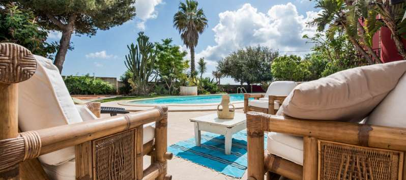 table and deckchairs in the villa with pool in Palermo