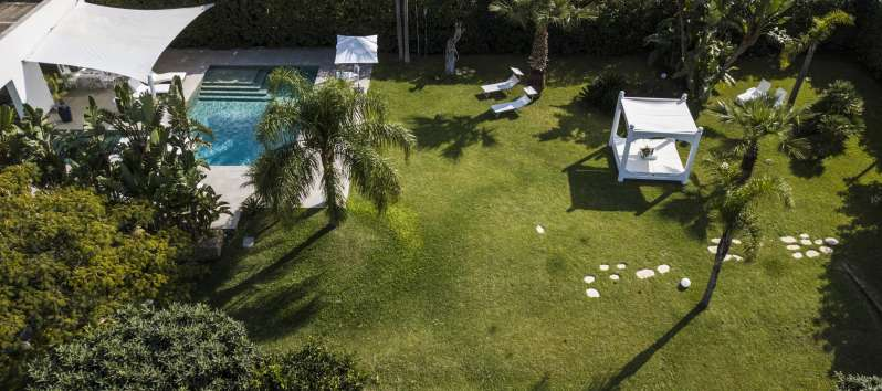 garden and pool with deckchairs of the villa in Palermo