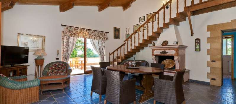 living room with wooden table and staircase in the villa with swimming pool in Trapani