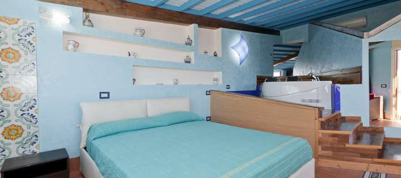 double bedroom with exposed beams in the villa with swimming pool in Trapani