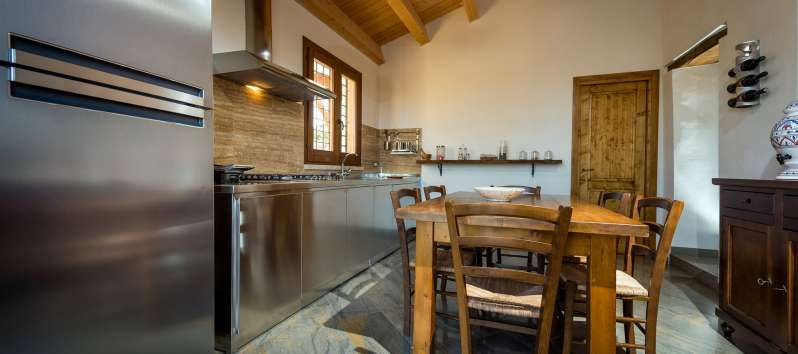 kitchen with wooden table in the villa with pool in Scopello