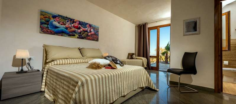 double bedroom with window in the villa with swimming pool in Scopello