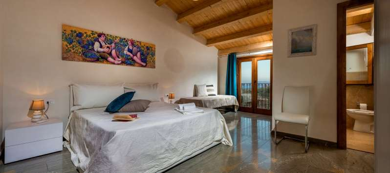 double bedroom with exposed beams in the villa with pool in Scopello