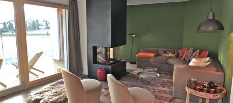 lounge with armchairs and fireplace in the apartment in the Engandine area