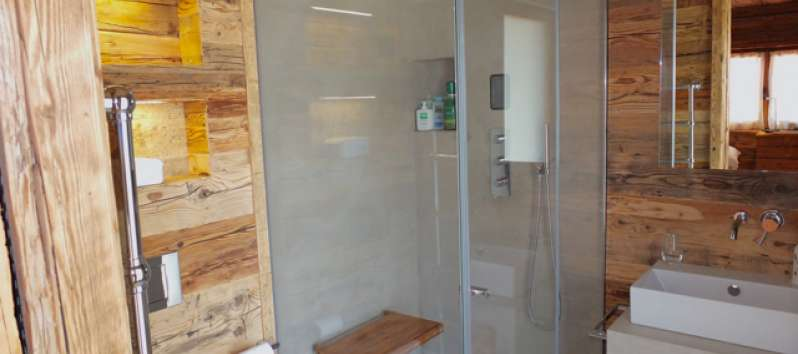 bathroom with glass shower in the apartment in Canton of Grisons