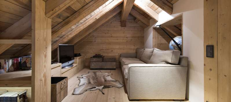 attic with sofa in the chalet in Surlej