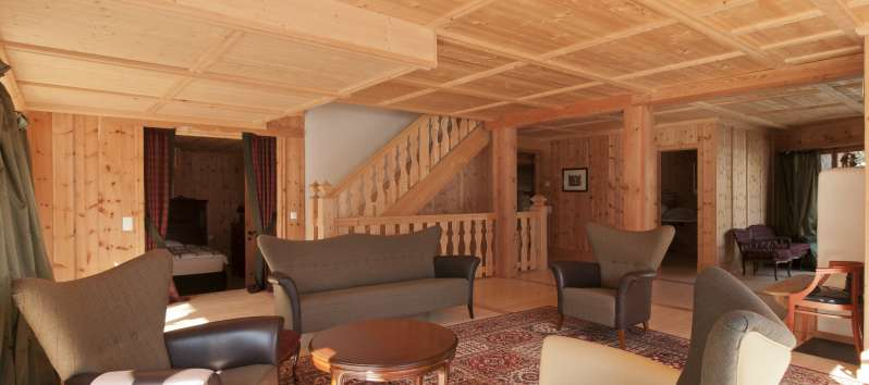 living room with wooden staircase in the villa in St. Moritz