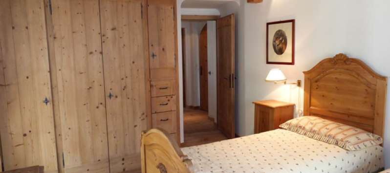 double bedroom with wooden wardrobe in the villa in Switzerland