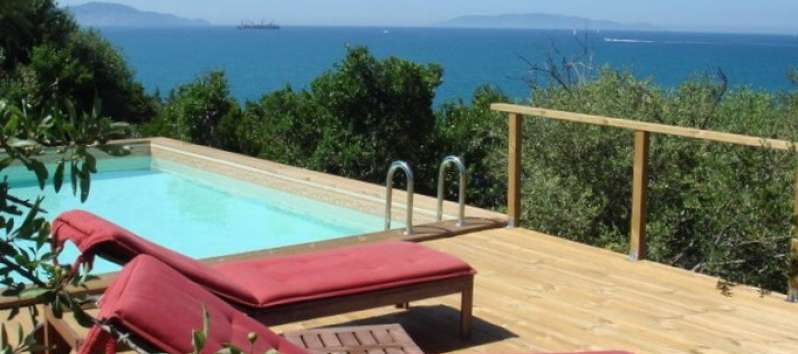 Villa Sara with decking and lounge chairs overlooking the sea