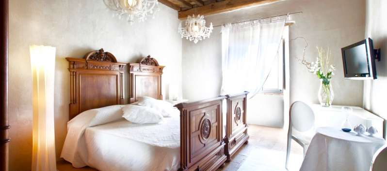 bedroom with exposed beams in the villa of Perugia